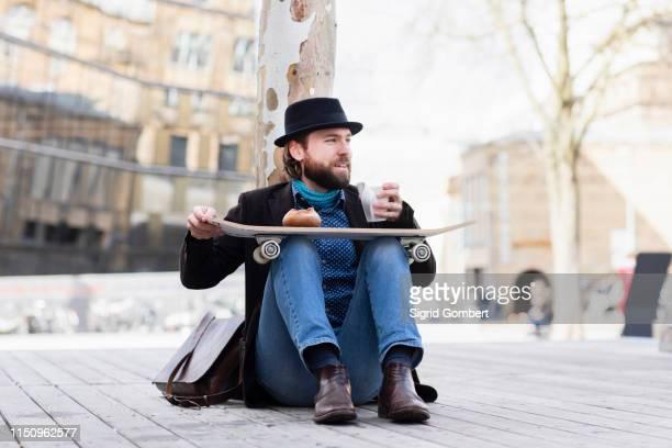 male skateboarder sitting in city square with takeaway drink, freiburg, baden-wurttemberg, germany - sigrid gombert stock-fotos und bilder
