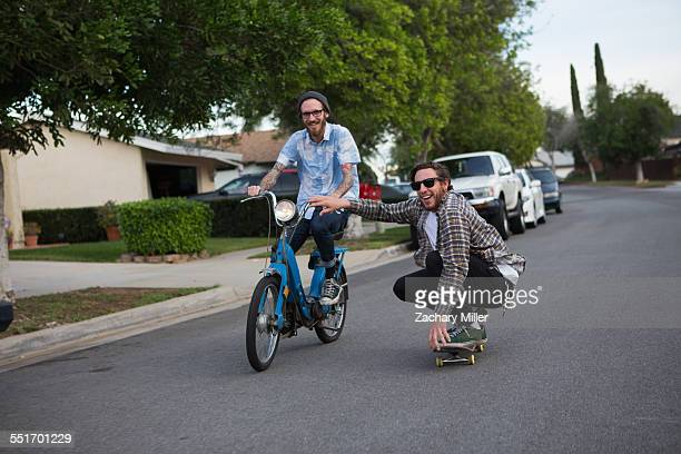 Male skateboarder skitching on friends moped along suburban road