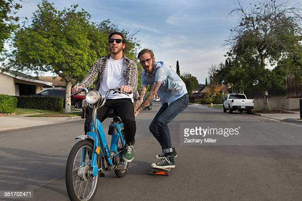 Male skateboarder skitching on friends moped on suburban road