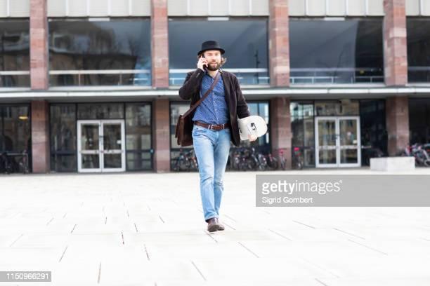 male skateboarder strolling in city square making smartphone call, freiburg, baden-wurttemberg, germany - sigrid gombert stock-fotos und bilder