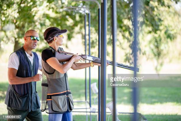 male skeet shooting instructor watching and guiding adult woman shooting on shooting range - trap shooting stock pictures, royalty-free photos & images