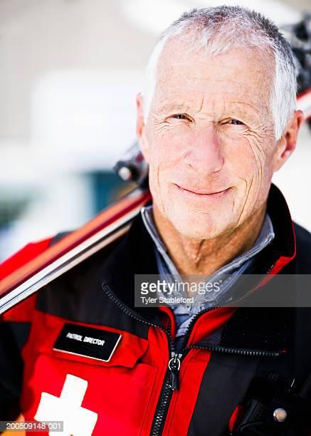 Male ski patroller holding skis over shoulder, smiling, portrait
