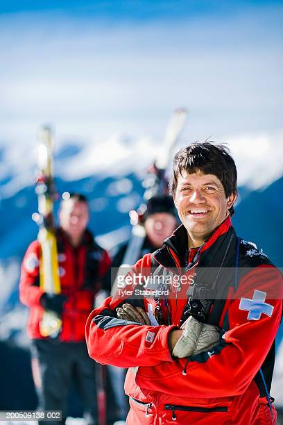 Male ski patroller on slope with colleagues, smiling, portrait