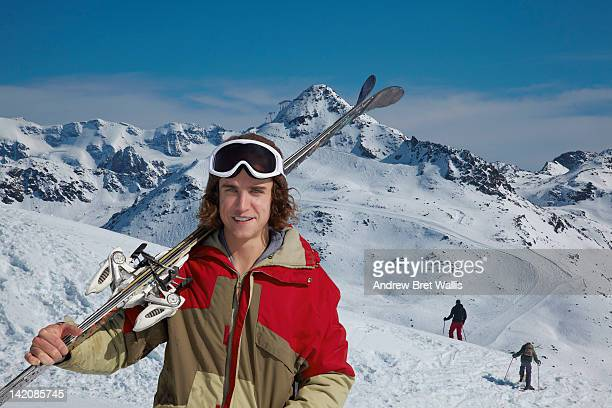 male skier carrying skis in the mountains - ski wear stock pictures, royalty-free photos & images