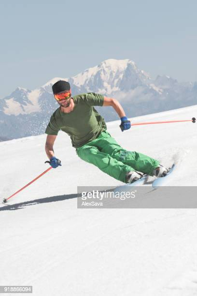 Male skier freeriding downhill snow-capped slope