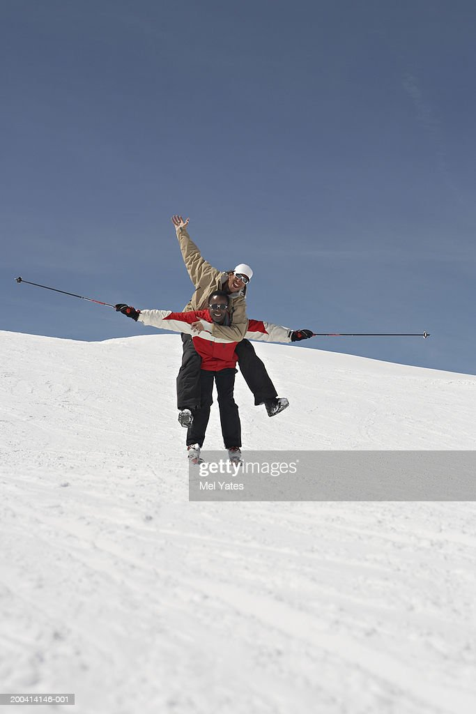 Male Skier Giving Man Piggy Back On Snow Covered Slope Smiling ...
