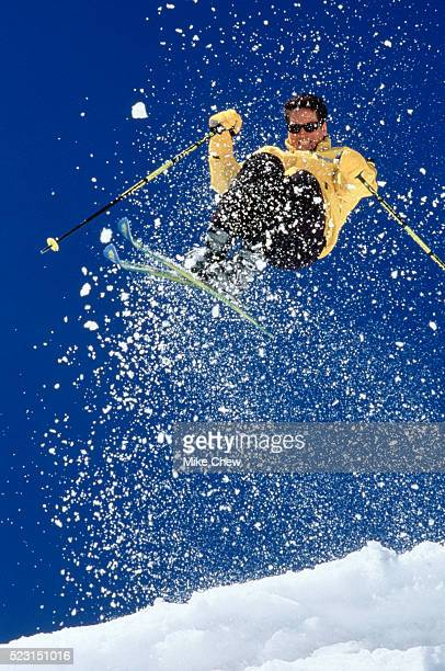 Male skier jumping off cornice