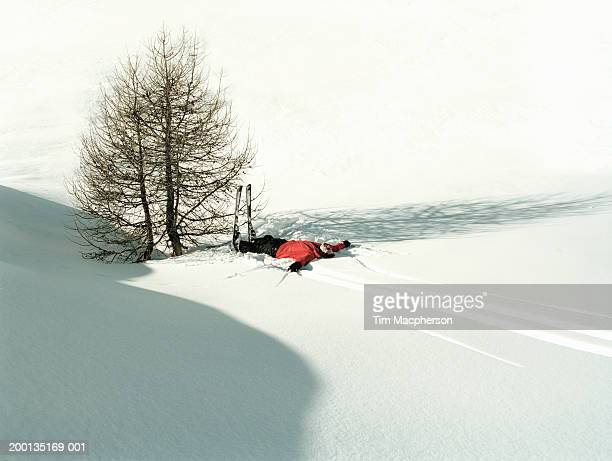 Male skier lying on back in snow by tree, elevated view