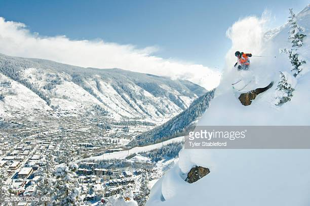 Male skier making steep powder turn
