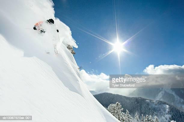 Male skier making steep powder turn