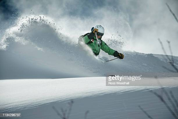 male skier skiing on snow covered mountain, alpe-d'huez, rhone-alpes, france - powder snow stock pictures, royalty-free photos & images