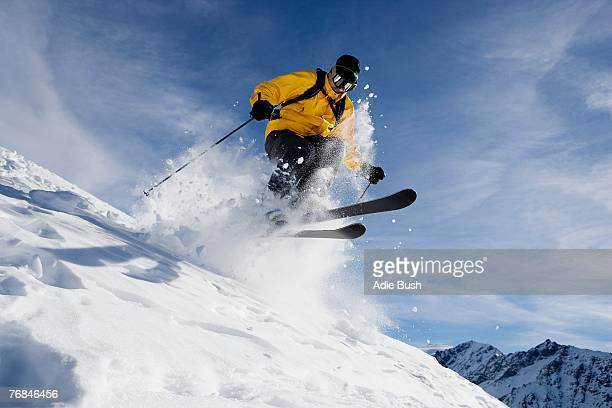 male skiing over mountain ridge - skiing stock pictures, royalty-free photos & images