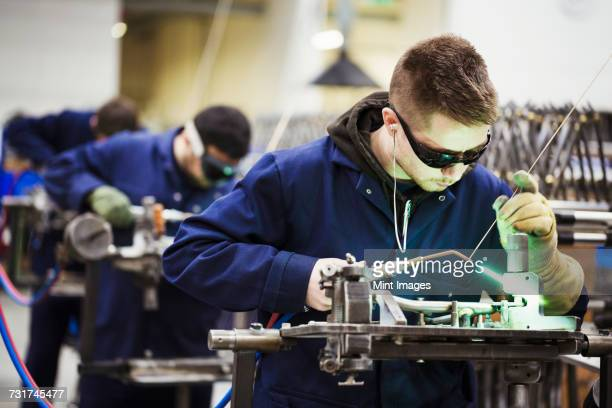Male skilled factory worker wearing protective glasses, welding part of a bicycle together in a factory.