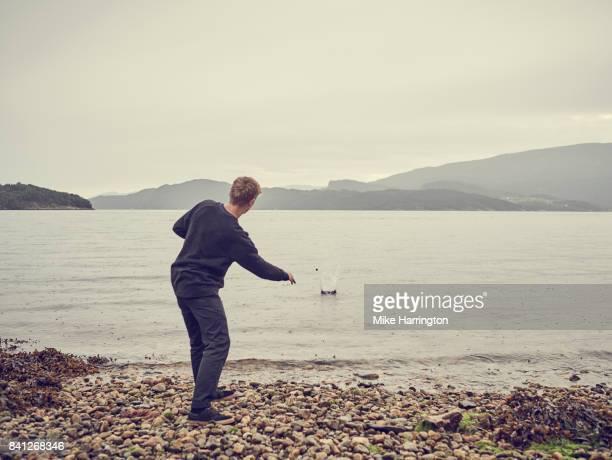 male skimming stones across lake - werfen stock-fotos und bilder