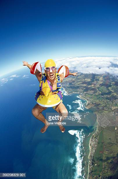 Male skydiver wearing water wings and inflatable ring, aerial view
