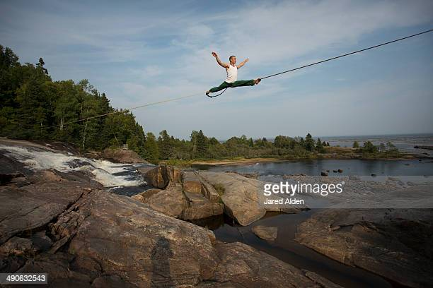 Male slackliner doing the splits on a long highline over water