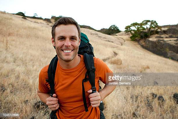 Male smiles while hiking in the outdoors.