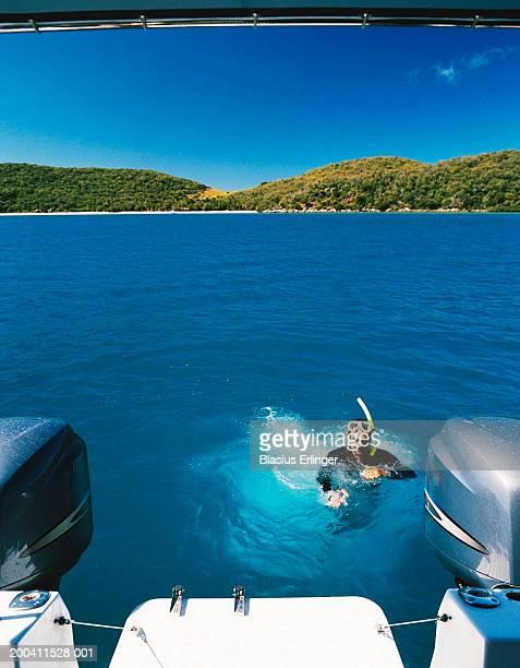 Male snorkeler behind motorboat