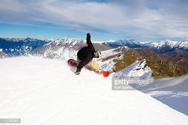 A male snowboarder blasts a heel side turn while snowboarding at Coronet Peak in Queenstown, New Zealand.