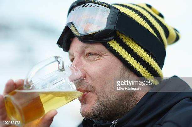 Male snowboarder enjoying a beer during Aprés Ski