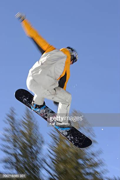 male snowboarder in mid air, rear view (blurred motion) - big air bildbanksfoton och bilder