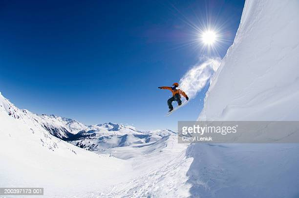 male snowboarder jumping off cornice, low angle view - boarding stock pictures, royalty-free photos & images