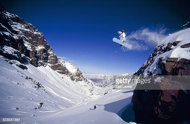Male snowboarder jumping off mountain, Jebel Toubkal, Morocco