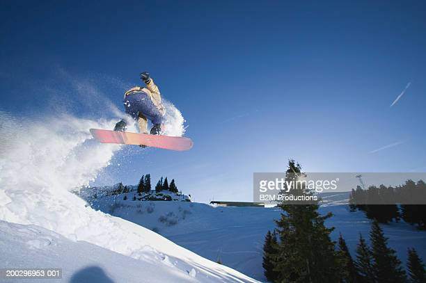 Male snowboarder jumping on slope, low angle view