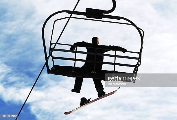 male snowboarder on ski lift, rear view - one man only stock pictures, royalty-free photos & images