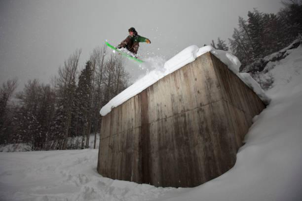 A male snowboarder rides off concrete building in Colorado.