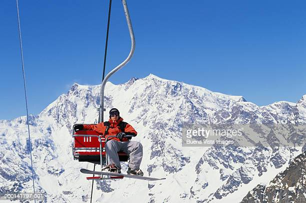 male snowboarder riding chair lift - ski lift stock pictures, royalty-free photos & images