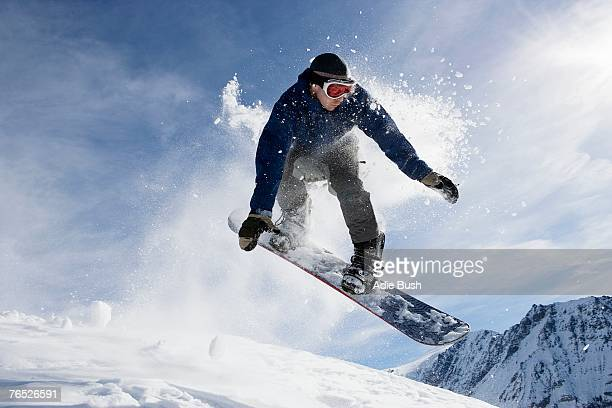 male snowboarding on mountain, action shot - boarding stock pictures, royalty-free photos & images