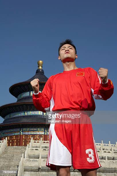 A male soccer athlete pumps his fists in celebration in front of Beijing's Temple of Heaven.