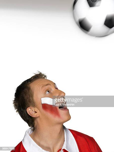 Young man with Poland flag painted on face playing with soccer ball