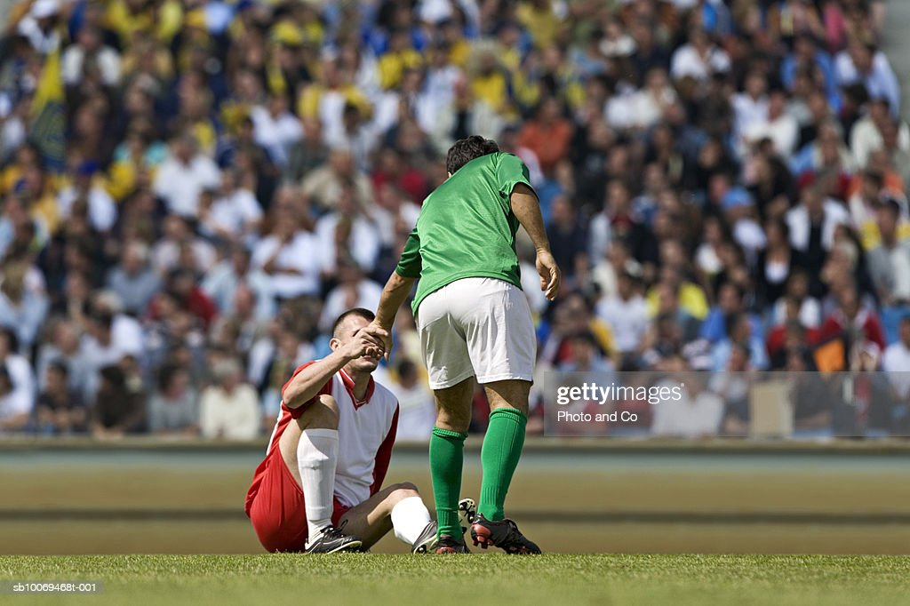 Male soccer player assisting opponent after tackle, in stadium : Stock Photo