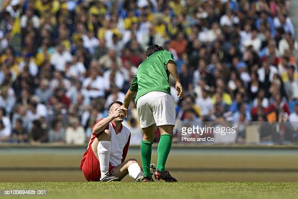 male soccer player assisting opponent after tackle, in stadium - rivaliteit stockfoto's en -beelden