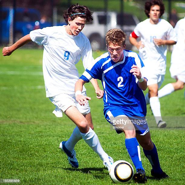 male soccer player challenges another player for ball from behind - face off sports play stock photos and pictures