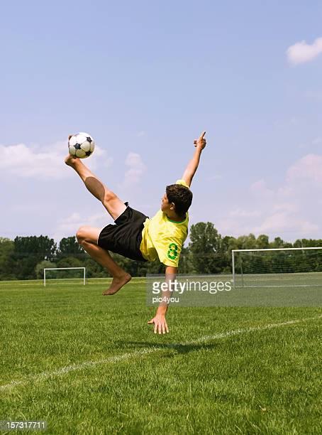 male soccer player doing a bicycle kick - stunt stockfoto's en -beelden