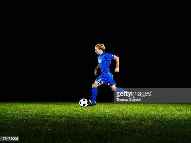 male soccer player dribbling ball - ドリブル ストックフォトと画像