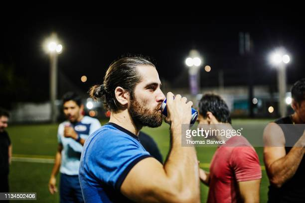 male soccer player drinking beer after nighttime game with friends - mexican beer stock pictures, royalty-free photos & images