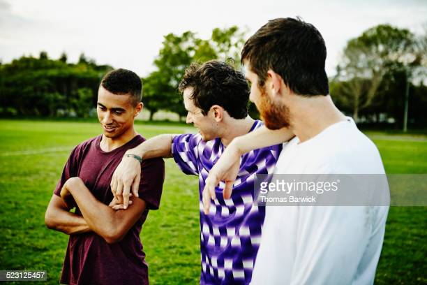 Male soccer player in discussion with teammates