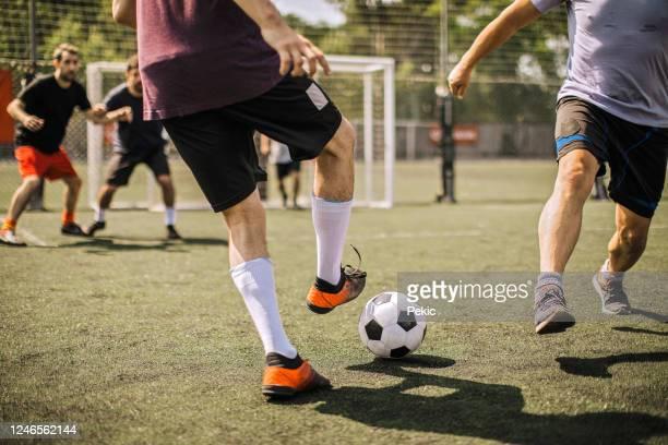 männlicher fußballer kickt fußball - treten stock-fotos und bilder