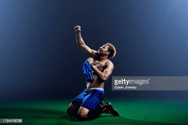 male soccer player kneeling with arm raised - scoring a goal stock pictures, royalty-free photos & images