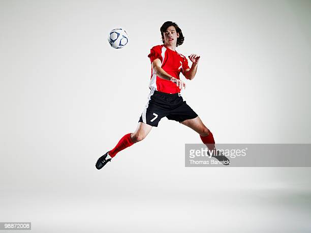 Male soccer player leaping and heading soccer ball