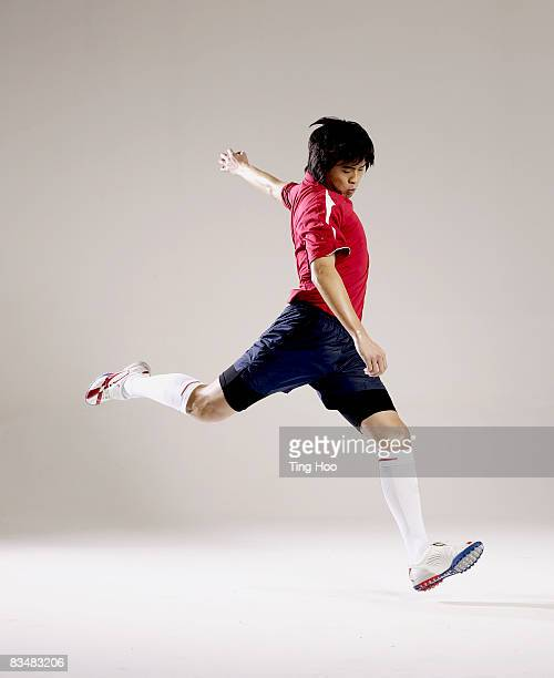 male soccer player preparing to kick ball - kicking stock pictures, royalty-free photos & images