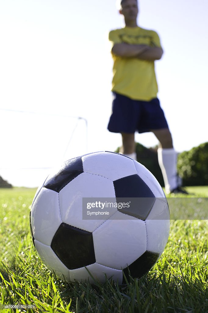 Male soccer player standing behind football, focus on ball : Stockfoto