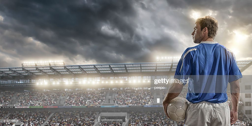 male soccer player standing in front of a large crowd : Stock Photo
