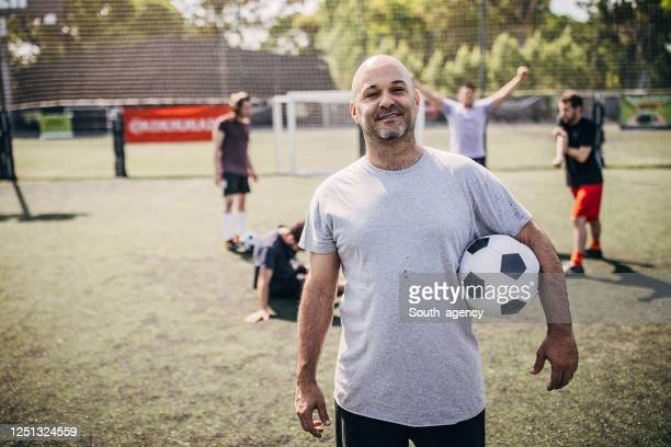 male soccer player standing on soccer field - football team stock pictures, royalty-free photos & images