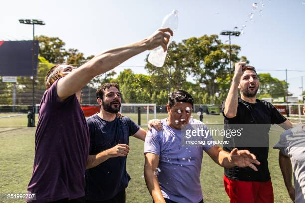 male soccer players cheering and celebrating victory at soccer field - friendly match stock pictures, royalty-free photos & images