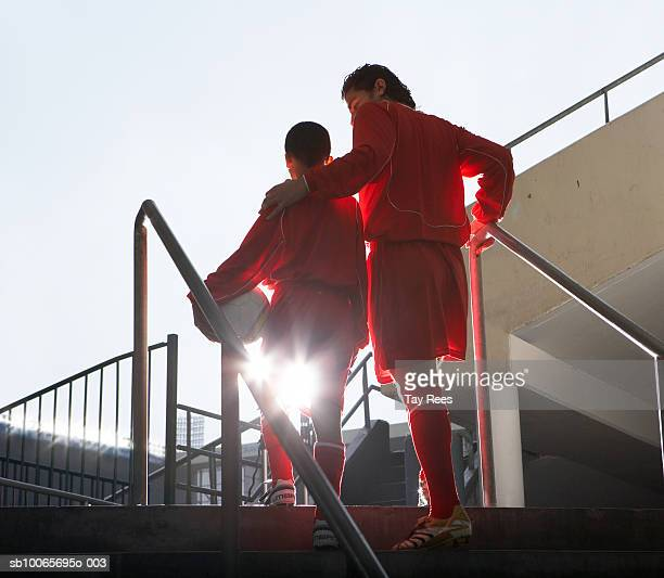Male soccer players entering stadium